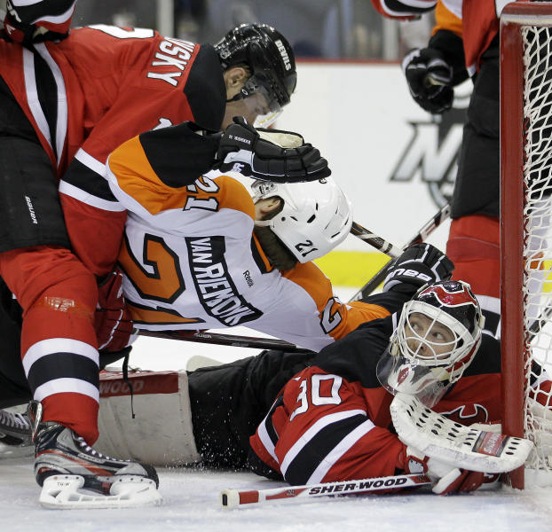 New Jersey Devils goalie Martin Brodeur, right, makes a save as teammate Alexei Ponikarovsky, left, of Ukraine, collides with Philadelphia Flyers' James van Riemsdyk during the first period of Game 4 of a second-round NHL hockey Stanley Cup playoff series, Sunday, May 6, 2012, in Newark, N.J. (AP Photo/Julio Cortez)