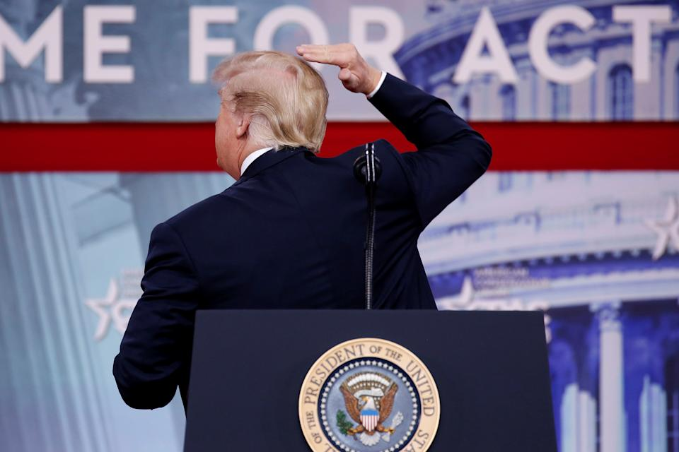 U.S. President Donald Trump pretends to smooth his hair as he speaks at the Conservative Political Action Conference (CPAC) at National Harbor, Maryland, U.S., February 23, 2018.      REUTERS/Joshua Roberts
