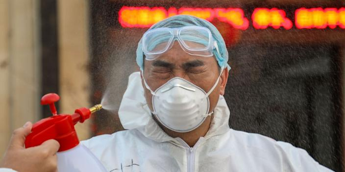 A doctor being disinfected by his colleague at a quarantine zone in Wuhan on January 3.