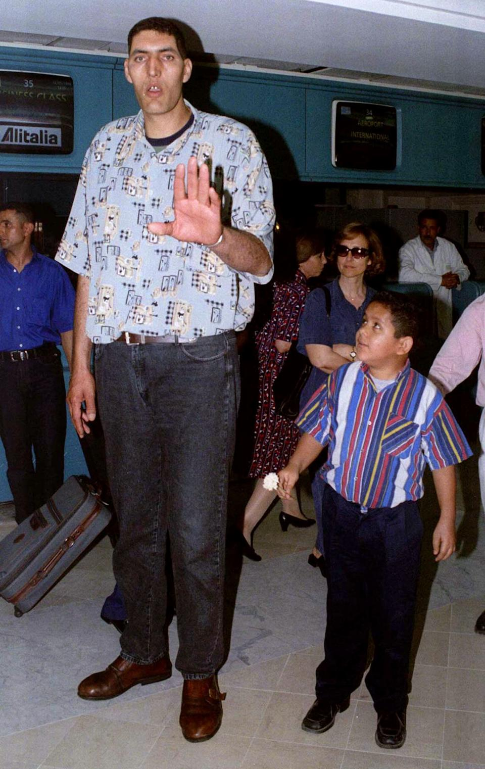 The World's tallest man, Tunisian Radhouan Charbib, gestures before catching a flight from Tunis' Carthage airport for London May 12 where he is due to attend a ceremony held by the Guinness Book of Records celebrating him officially as the Tallest Man in the World. Charbib, 29, stands at 2.35 metres and weighs 160 kgs. He takes over the throne in the Guinness Book from Pakistani Alan Channa 2.32 metres.