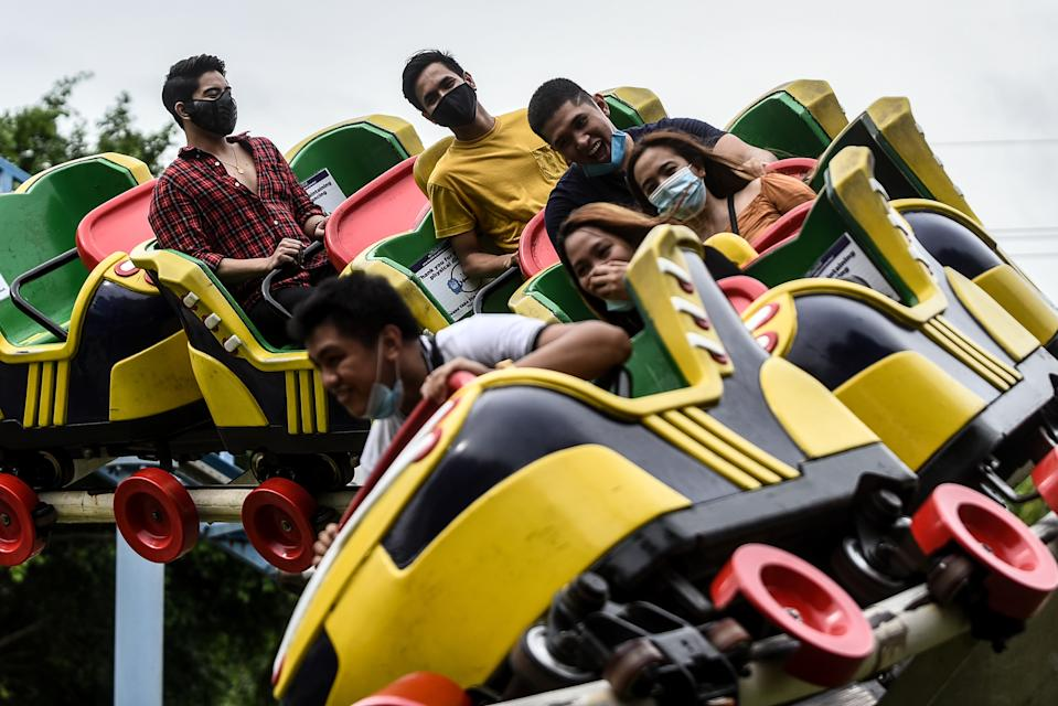 People wearing face masks take a ride at Enchanted Kingdom, an amusement park in the province of Laguna in the Philippines, on October 18, 2020. Guests aged 21-59 are allowed to enter the amusement park, while minors and senior citizens are restricted as per guidelines.(Photo by Lisa Marie David/NurPhoto via Getty Images)