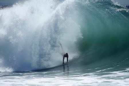 """A swimmer catches a wave at """"The Wedge"""" wave break in Newport Beach, California August 27, 2014. REUTERS/Lucy Nicholson"""