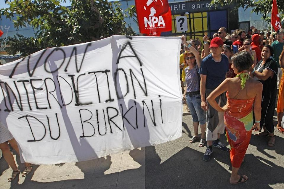 """People hold a banner reading """"No to the ban on burkinis"""" in front of Port-Leucate city hall in Leucate, southern France, on August 25, 2016 (AFP Photo/Raymond Roig)"""