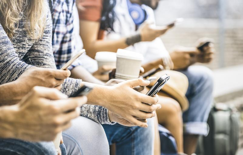 Young people sitting on a bench and using their smartphones.