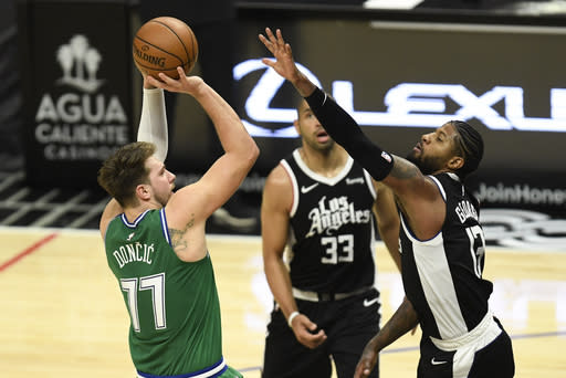 Dallas Mavericks guard Luka Doncic, left, shoots over Los Angeles Clippers guard Paul George during the first half of an NBA basketball game in Los Angeles, Sunday, Dec. 27, 2020. (AP Photo/Kyusung Gong)