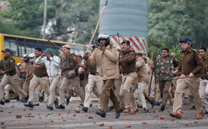 FILE PHOTO: Police officers chase protestors during a protest against the Citizenship Amendment Bill in New Delhi