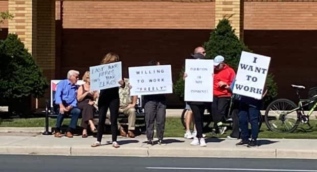 Dozens of people gathered outside of Windsor Regional Hospital's Met campus on Wednesday, protesting the hospital's suspension of unvaccinated staff.  (Jason Viau/CBC - image credit)