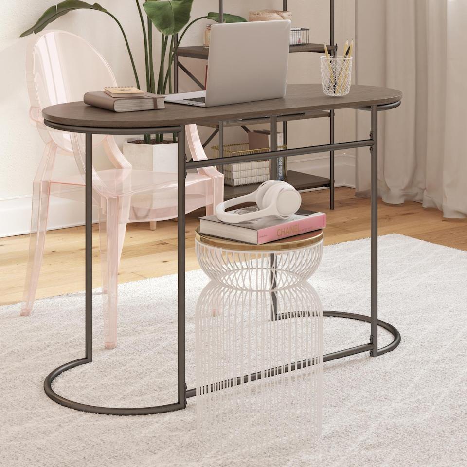 """<h3>CosmoLiving Vivinne Writing Desk</h3><br>This sleek metal and wood workspace boasts major space-optimizing potential with its rounded narrow structure and open-design frame.<br><br><strong>CosmoLiving by Cosmopolitan</strong> Vivinne Writing Desk, $, available at <a href=""""https://go.skimresources.com/?id=30283X879131&url=https%3A%2F%2Fwww.overstock.com%2FHome-Garden%2FCosmoLiving-by-Cosmopolitan-Vivinne-Writing-Desk%2F30813142%2Fproduct.html"""" rel=""""nofollow noopener"""" target=""""_blank"""" data-ylk=""""slk:Overstock.com"""" class=""""link rapid-noclick-resp"""">Overstock.com</a>"""