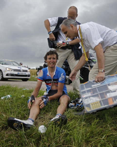 A doctor tends to Johan van Summeren of Belgium after a crash in the pack at some 25 kilometers from the finish line during the sixth stage of the Tour de France cycling race over 207.5 kilometers (129 miles) with start in Epernay and finish in Metz, France, Friday July 6, 2012. ( (AP Photo/Laurent Cipriani)