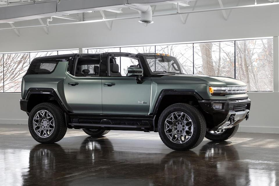 A green electric Hummer SUV from GMC sitting in an empty showroom