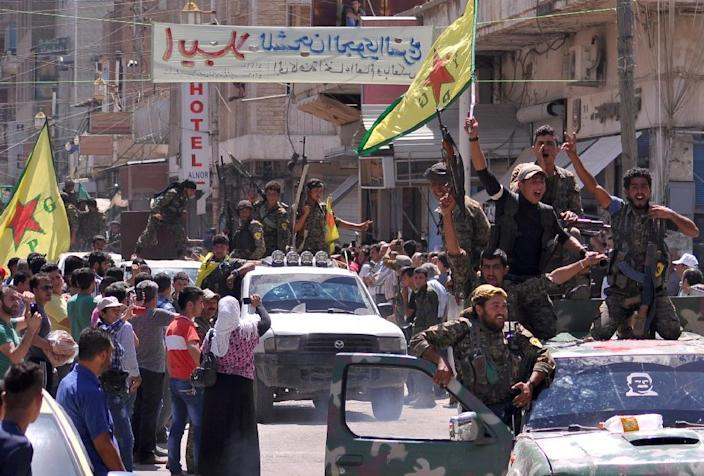 Kurdish People's Protection Units (YPG) fighters parade in the Syrian town of Qamishli after returning from battling Islamic State group jihadists on the border with Turkey on June 24, 2015 (AFP Photo/Delil Souleiman)
