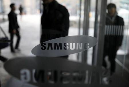 Shareholders walk past the logo of Samsung Electronics before their general meeting at a company's building in Seoul