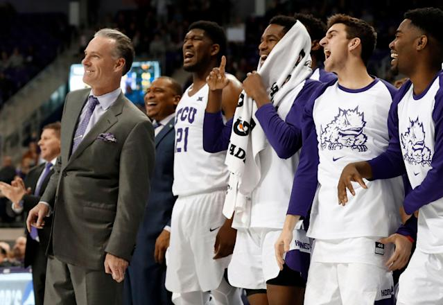 TCU head coach Jamie Dixon, left, Kevin Samuel (21) and the rest of the bench watch in the final moments of their NCAA college basketball game against West Virginia on Tuesday, Jan. 15, 2019, in Fort Worth, Texas. TCU won 98-67. (AP Photo/Tony Gutierrez)