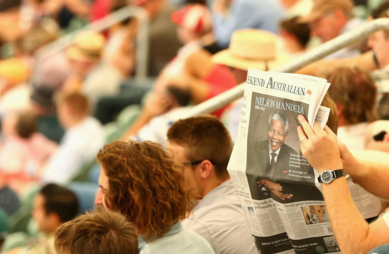 ADELAIDE, AUSTRALIA - DECEMBER 07:  A spectator reads a newspaper honoring the late Nelson Madela during day three of the Second Ashes Test match between Australia and England at Adelaide Oval on December 7, 2013 in Adelaide, Australia.  (Photo by Ryan Pierse/Getty Images)