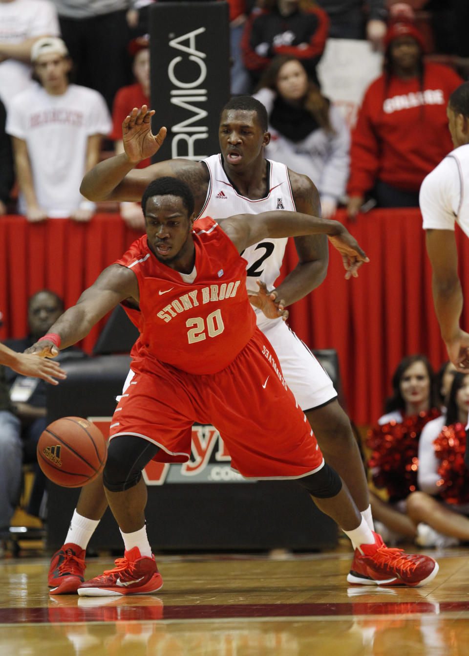 Stony Brook forward Jameel Warney (20) goes after the ball while being covered by Cincinnati center Coreontae DeBerry (22) in the first half of an NCAA college basketball game, Tuesday, Dec. 2, 2014, in Cincinnati. (AP Photo/Frank Victores)