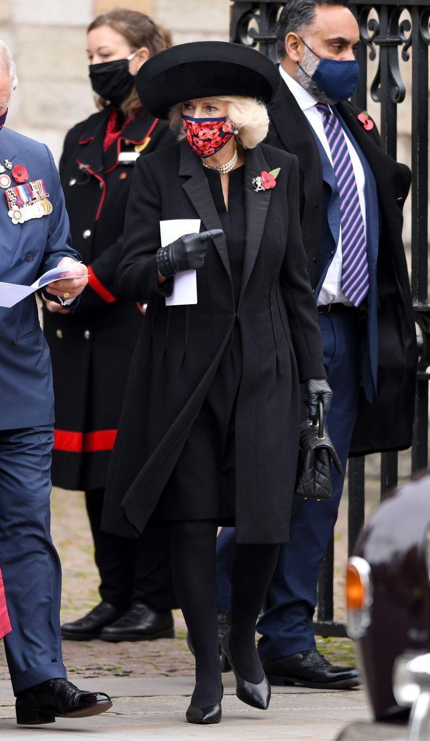 <p>Camilla paired an all-black look with pearl strands and a structured black hat for a commemoration of the Centenary of the Burial of the Unknown Warrior at Westminster Abbey. She adorned the look with a symbolic poppy brooch and a matching poppy-print face mask.</p>