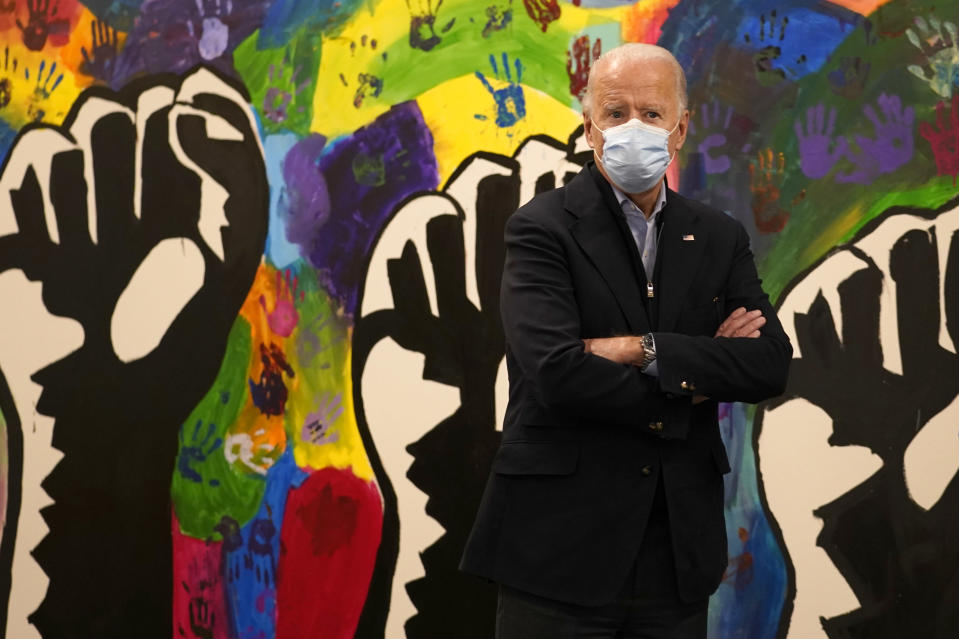 FILE - In this Nov. 3, 2020, file photo, Democratic presidential candidate former Vice President Joe Biden pauses in front of a mural during visit to The Warehouse teen center in Wilmington, Del. A tough road lies ahead for Biden who will need to chart a path forward to unite a bitterly divided nation and address America's fraught history of racism that manifested this year through the convergence of three national crises. (AP Photo/Carolyn Kaster, File)