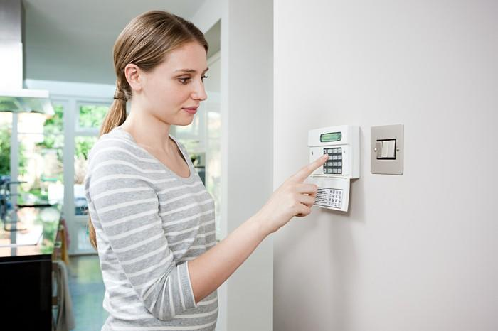 A woman programs her home security system.