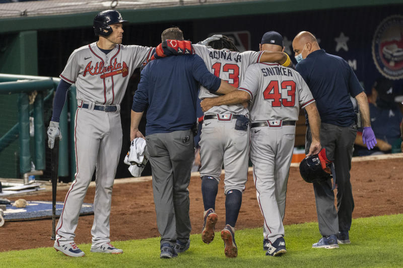Atlanta Braves' Freddie Freeman, left, taps the head of Ronald Acuna Jr. (13) as Acuna is helped out of the field after fouling a ball off his left foot during the fourth inning of the team's baseball game against the Washington Nationals in Washington, Friday, Sept. 11, 2020. (AP Photo/Manuel Balce Ceneta)