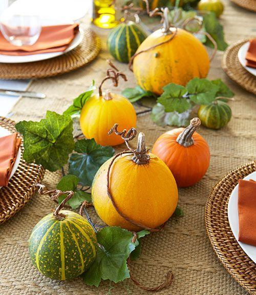 """<p>Dress up the dinner table with a fast autumnal centerpiece. Just coil <span class=""""redactor-unlink"""">wire vines</span> around gourds' stems, then weave in a faux ivy garland for extra greenery. </p>"""
