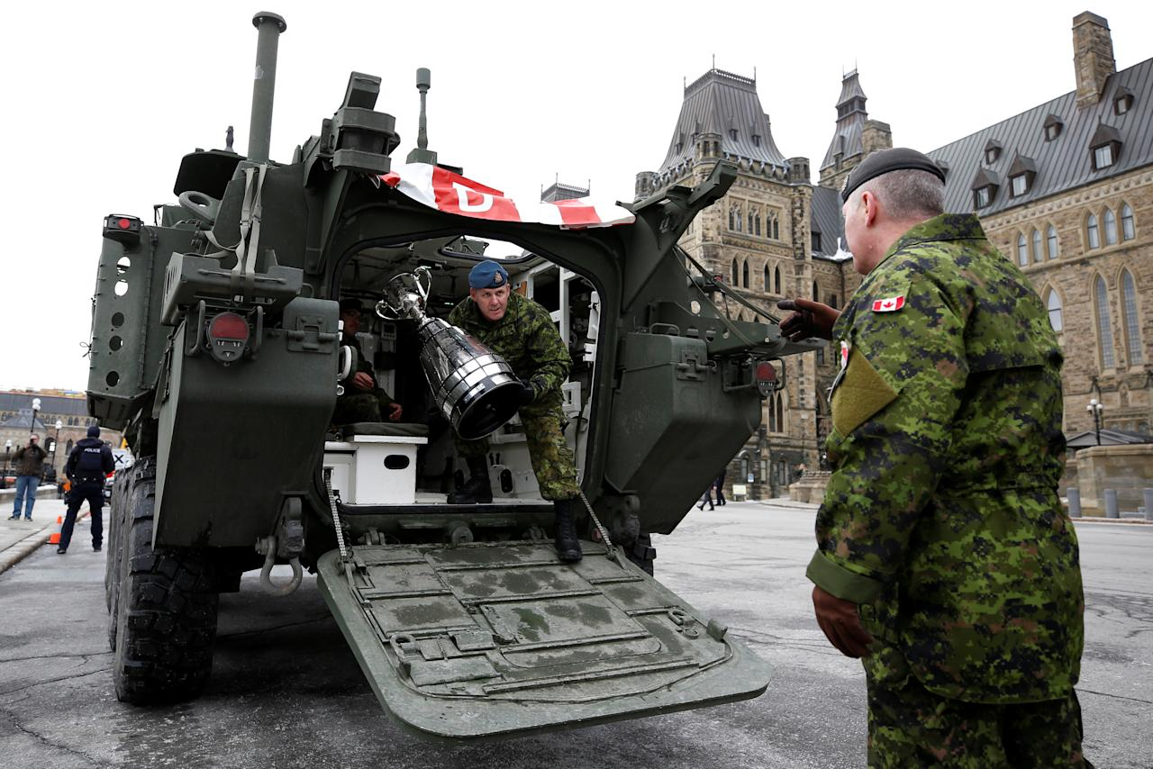A member of the Canadian Armed Forces carries the CFL's Grey Cup trophy as it arrives for a ceremony on Parliament Hill in Ottawa, Ontario, Canada, November 21, 2017. REUTERS/Chris Wattie