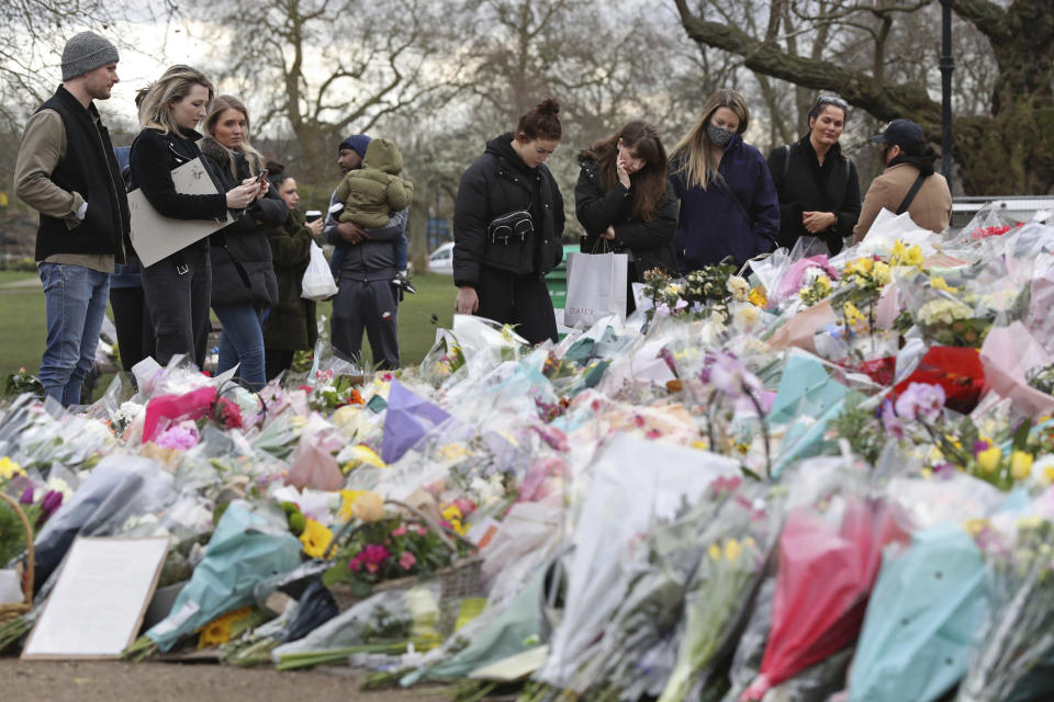 People gather to view and read inscriptions on floral tributes for murdered Sarah Everard, at the bandstand in Clapham Common, London