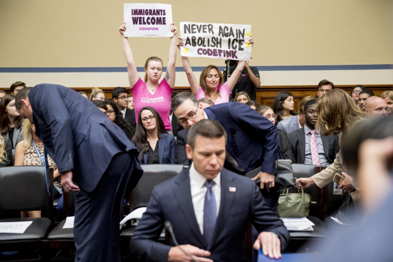 """Activists with Code Pink hold up signs that read """"Immigrants Welcome"""" and """"Never Again Abolish ICE"""" as Acting Secretary of Homeland Security Kevin McAleenan arrives to testify before a House Committee on Oversight and Reform hearing on Capitol Hill in Washington, Thursday, July 18, 2019. (AP Photo/Andrew Harnik)"""