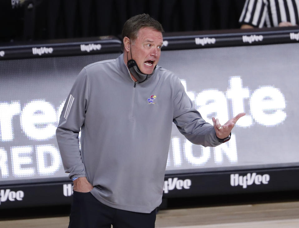 Bill Self gestures with his hand and says something with his face mask down.