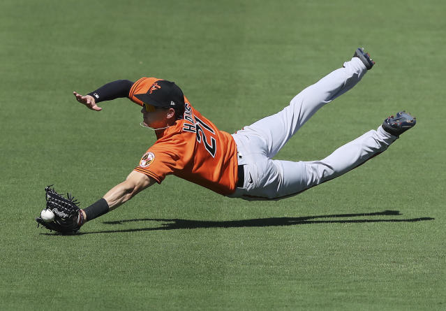 Baltimore Orioles outfielder Austin Hays can't quite get to a ball hit for an RBI single by Atlanta Braves Adam Duvall during the first inning in a MLB spring training baseball game Saturday, Feb. 22, 2020, in North Port, Fla. (Curtis Compton/Atlanta Journal-Constitution via AP)