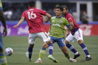 Seattle Sounders forward Fredy Montero (12) kicks the ball from between FC Dallas forward Ricardo Pepi (16) and midfielder Facundo Quignon (5) during the first half of an MLS soccer match Wednesday, Aug. 4, 2021, in Seattle. (AP Photo/Ted S. Warren)