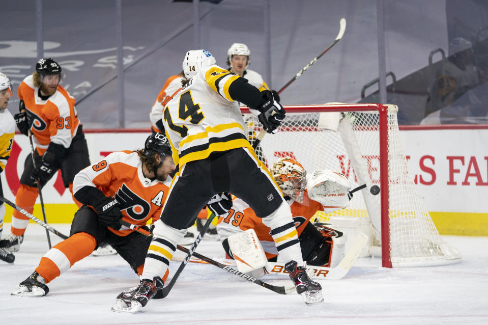 Pittsburgh Penguins' Mark Jankowski, center, shoots the puck past Philadelphia Flyers' goaltender Carter Hart, right, for a goal during the first period of an NHL hockey game, Wednesday, Jan. 13, 2021, in Philadelphia. (AP Photo/Chris Szagola)