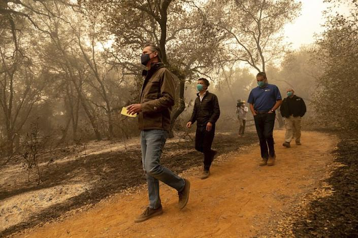 Gov. Gavin Newsom takes notes as he tours the North Complex Fire zone