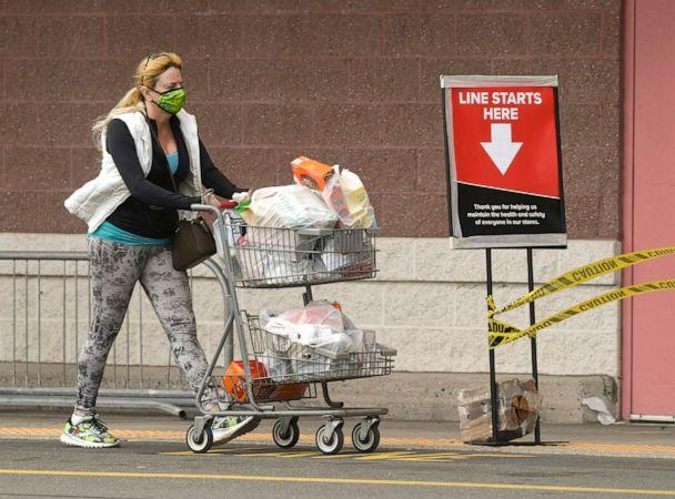 PHOTO: A woman wearing a face mask pushes a cart of groceries past the front of the Giant Supermarket in Spring Township, Pa., April 15, 2020. (Reading Eagle/MediaNews Group via Getty Images)