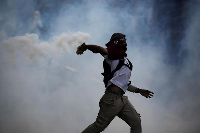 <p>Demonstrator throws back a tear gas canister during rally against Venezuela's President Nicolas Maduro in Caracas, Venezuela May 1, 2017. (Photo: Marco Bello/Reuters) </p>