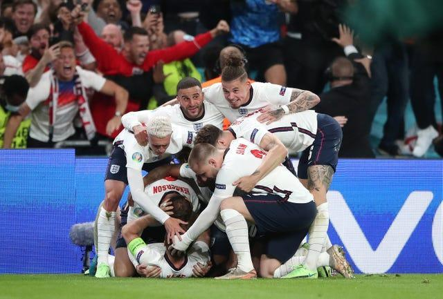 England's Harry Kane is mobbed by team-mates