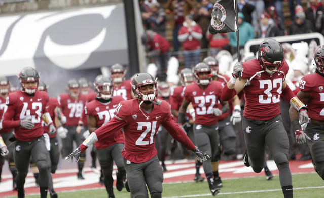 FILE - In this Nov. 4, 2017, file photo, Washington State cornerback Marcellus Pippins (21), linebacker Dylan Hanser (33) and teammates run onto the field before an NCAA college football game against Stanford in Pullman, Wash. An internal audit has found extensive mismanagement within the budget-challenged Washington State athletic department, including the possible inflation of home football attendance figures and the improper distribution of free tickets to football games.7. (AP Photo/Young Kwak, File)