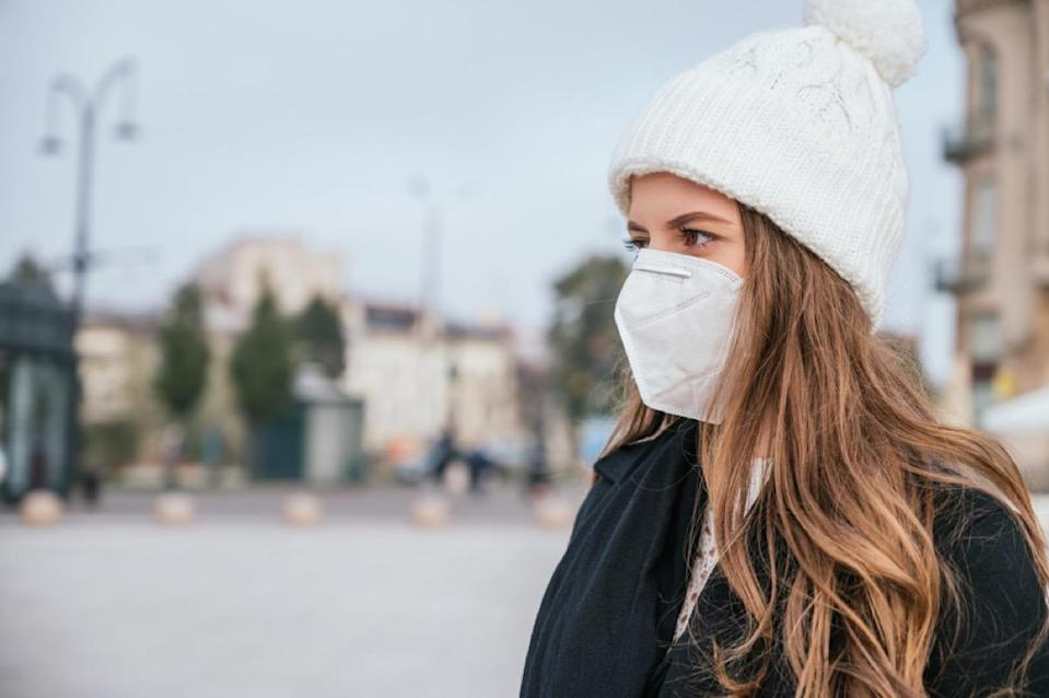 woman wearing a face mask and winter clothes outside
