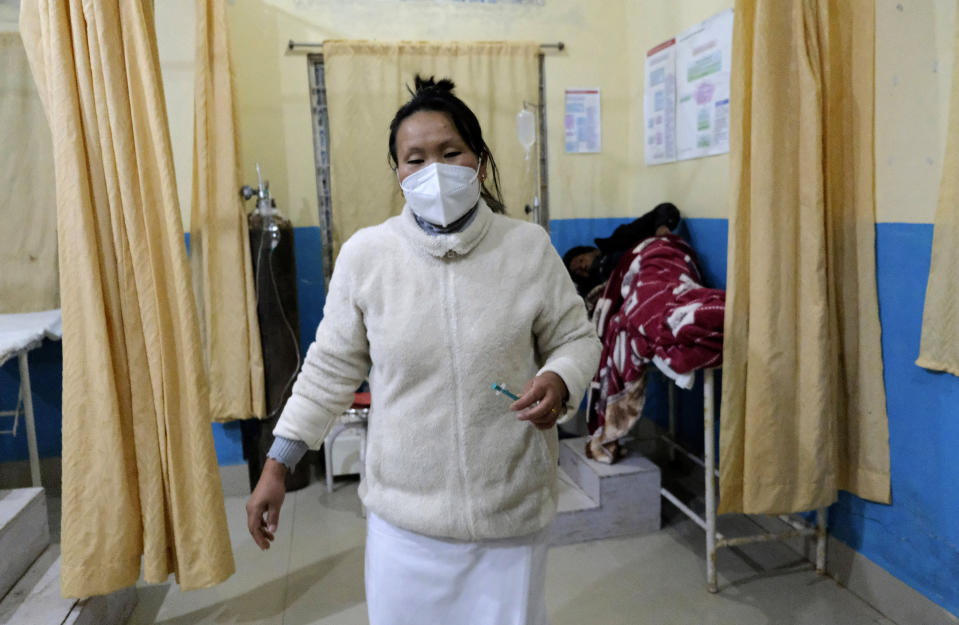Shimray Wungreichon, 43, holds a syringe after administering a shot to an elderly patient, while being the only nurse on overnight shift in the emergency ward at the District Hospital in Ukhrul, in the northeastern Indian state of Manipur, Friday, Jan. 15, 2021. Wungreichon was among the first of many Indian health workers to be vaccinated on Saturday, opening a new chapter in the battle against the pandemic in the world's second hardest-hit country, which has been scarred profoundly by a virus that has killed more than 152,000 of its people. (AP Photo/Yirmiyan Arthur)