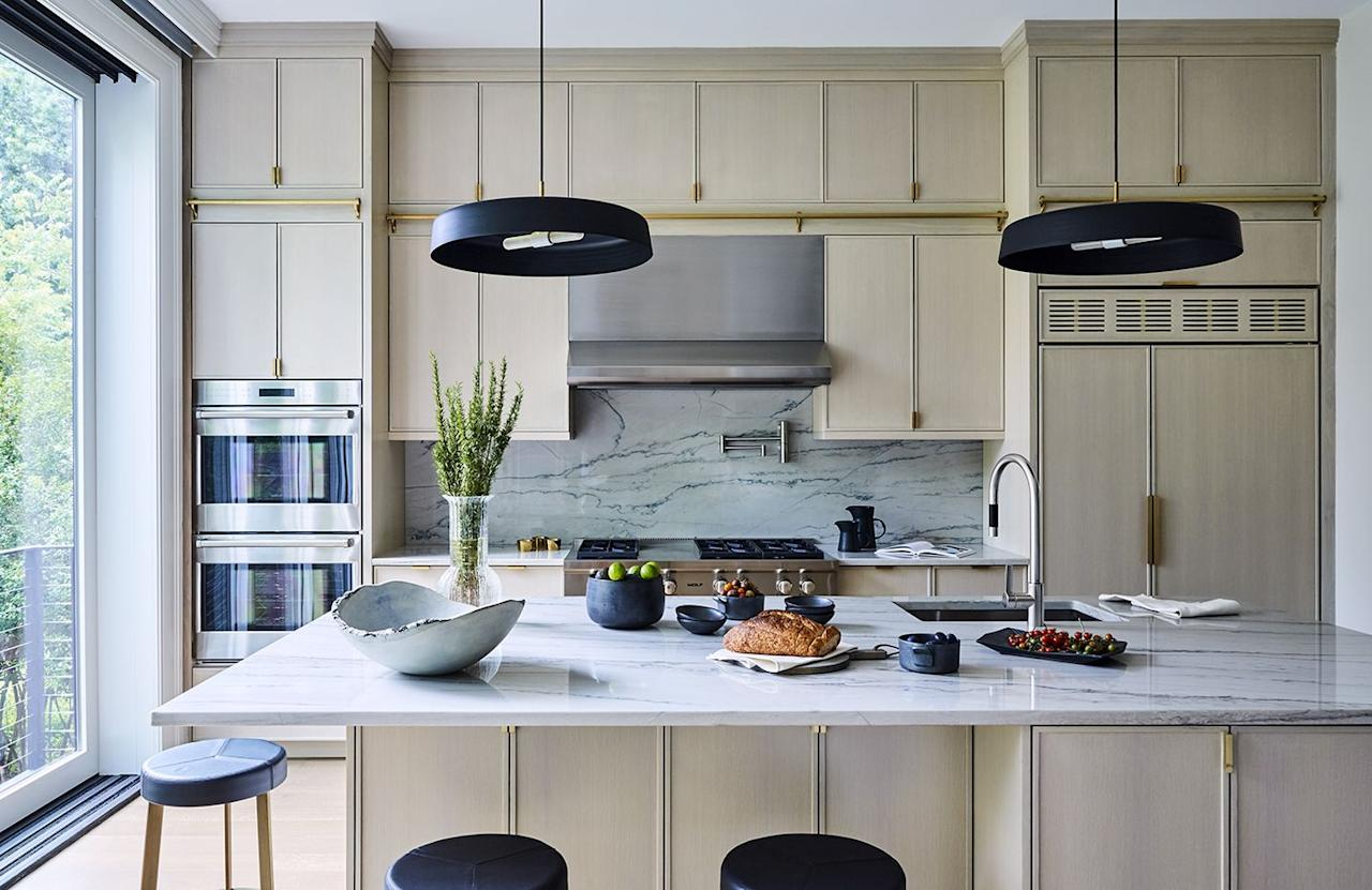 <p>In the kitchen, natural light complements the custom cerused oak kitchen cabinetry with custom brass detailing. Circular pendant lights from Lambert & Fils provide contrast and bring out streaks of black in the marble countertops and backsplash from Marble America in New Rochelle, New York. The stools were sourced from CB2, and the appliances, Wolf.</p>