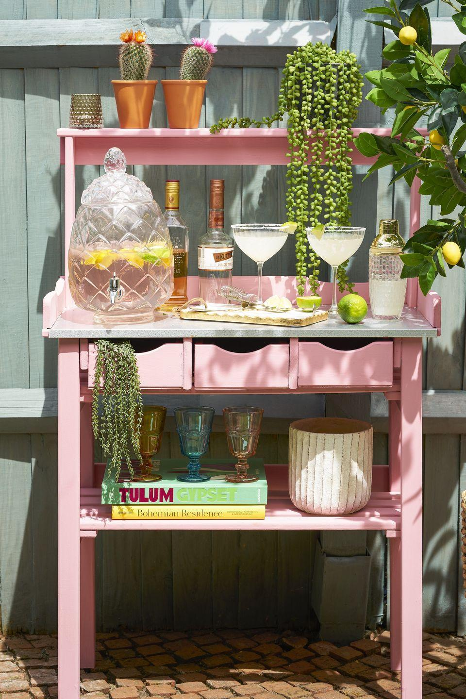 """<p>Want space for entertaining in your garden? Transform your space with a DIY cocktail bar.</p><p>'There's no need to invest in a pricey readymade bar when you can update a cheap and cheerful potting bench by day into a chic drinks station by night with a simple, purse-friendly lick of paint,' says <a href=""""https://go.redirectingat.com?id=127X1599956&url=https%3A%2F%2Fwww.wayfair.co.uk%2F&sref=https%3A%2F%2Fwww.redonline.co.uk%2Finteriors%2Feditors_choice%2Fg35933369%2Fgarden-ideas-on-a-budget%2F"""" rel=""""nofollow noopener"""" target=""""_blank"""" data-ylk=""""slk:Wayfair"""" class=""""link rapid-noclick-resp"""">Wayfair</a>'s Resident Style Advisor, Nadia McCowan Hill.</p><p>'A good quality primer & undercoat will remove the need for laborious sanding, so all you need to think about is selecting your go-to hue. Miami pink will add a retro flavour to your bar, whereas cornflower blue is the perfect tone for an English garden spritz and pistachio tones will blend seamlessly with spring foliage. Don't forget to seal your bar with a waterproof finishing wax to keep the sundowner sessions flowing summer after summer.'</p><p>And, of course, don't forget to style it: Add a drinks dispenser, coloured glassware and your favourite beverages – and finish off with succulents and greenery.</p>"""