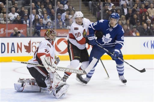 Ottawa Senators goaltender Craig Anderson, left, makes a save as Sergei Gonchar, center, bumps Toronto Maple Leafs' Nikolai Kulemin during the second period of an NHL hockey game in Toronto on Saturday, Feb. 16, 2013. (AP Photo/The Canadian Press, Chris Young)