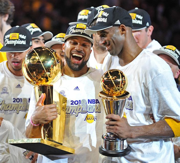 Los AngeLakers Derek Fisher and MVP Kobe Bryant hold the team and MVP trophies.
