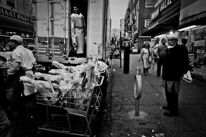 <p>Meat is unloaded from a delivery truck on 73rd Street in an area known as Little Bangladesh, in Jackson Heights, Queens, N.Y., in December 2015. (Photo: Yunghi Kim/Contact Press Images) </p>