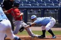 Boston Red Sox' Chad De La Guerra (95) is back to first base safely ahead of the throw to Tampa Bay Rays first baseman Yoshi Tsutsugo (25) in the second inning of a spring training baseball game on Friday, March 26, 2021, in Port Charlotte, Fla. (AP Photo/John Bazemore)