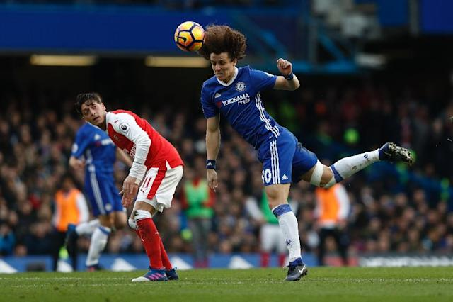Arsenal's Mesut Ozil (left) looks on as Chelsea's David Luiz heads the ball during their side's English Premier League football match at Stamford Bridge in London, on February 4, 2017 (AFP Photo/Adrian DENNIS)