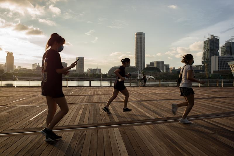 SINGAPORE - 2020/05/16: People wearing face mask as a preventive measure jog outside Marina Bay Sands during the Coronavirus (COVID-19) crisis. Singapore has so far confirmed 27,356 coronavirus cases, 22 deaths and 8,342 recovered, based on the latest update by the country's Ministry of Health. (Photo by Maverick Asio/SOPA Images/LightRocket via Getty Images)