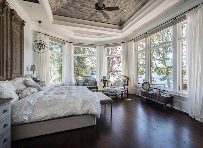 A large Victorian-style bedroom adorned with lots of white decor pieces and sleek hanging fixtures.