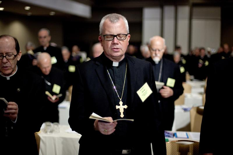 Auxiliary Bishop at Archdiocese of Milwaukee Donald Hying joins a prayer during the U.S. Conference of Catholic Bishops' biannual meeting Wednesday, June 13, 2012, in Atlanta. The national gathering is the bishops' first since dioceses filed a dozen lawsuits against an Obama administration mandate that most employers provide health insurance covering birth control. The rule generally exempts houses of worship, but faith-affiliated hospitals, charities and schools would have to comply. (AP Photo/David Goldman)