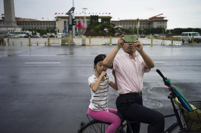 Onlookers take photographs near to an area where access has been blocked to the public in Tiananmen Square in China's capital Beijing on September 1, 2015 (AFP Photo/Fred Dufour)