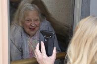 Laura Coriddi shows a photo on her phone through a window to her mother Emma Sahl at Northgate Healthcare facility Saturday, March. 6, 2021, in North Tonawanda N.Y. High rates of COVID-19 throughout New York have left the majority of its nursing homes closed for most indoor visits despite relaxed guidance meant to help open them up for visitors. New York updated its visitation rules Thursday, March 25 in a way that will now allow visits to resume under certain conditions, even if a resident has recently tested positive. (AP Photo/Jeffrey T. Barnes)